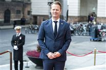 Jeppe Kofod iført blåt jakkesæt under åbningen af folketinget. Han smiler til fotograferne.