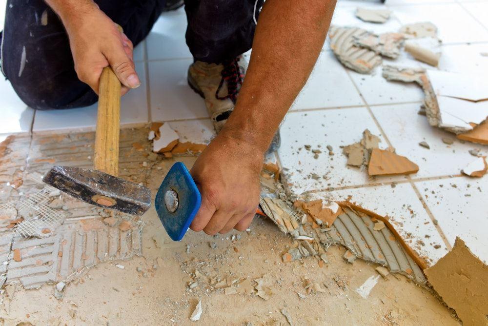 En håndværker banker gamle klinker af et gulv