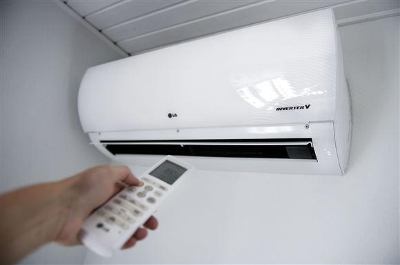 person med fjernbetjening rettet mod varmepumpe