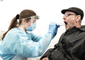 mand åbner munden for at blive testet for corona