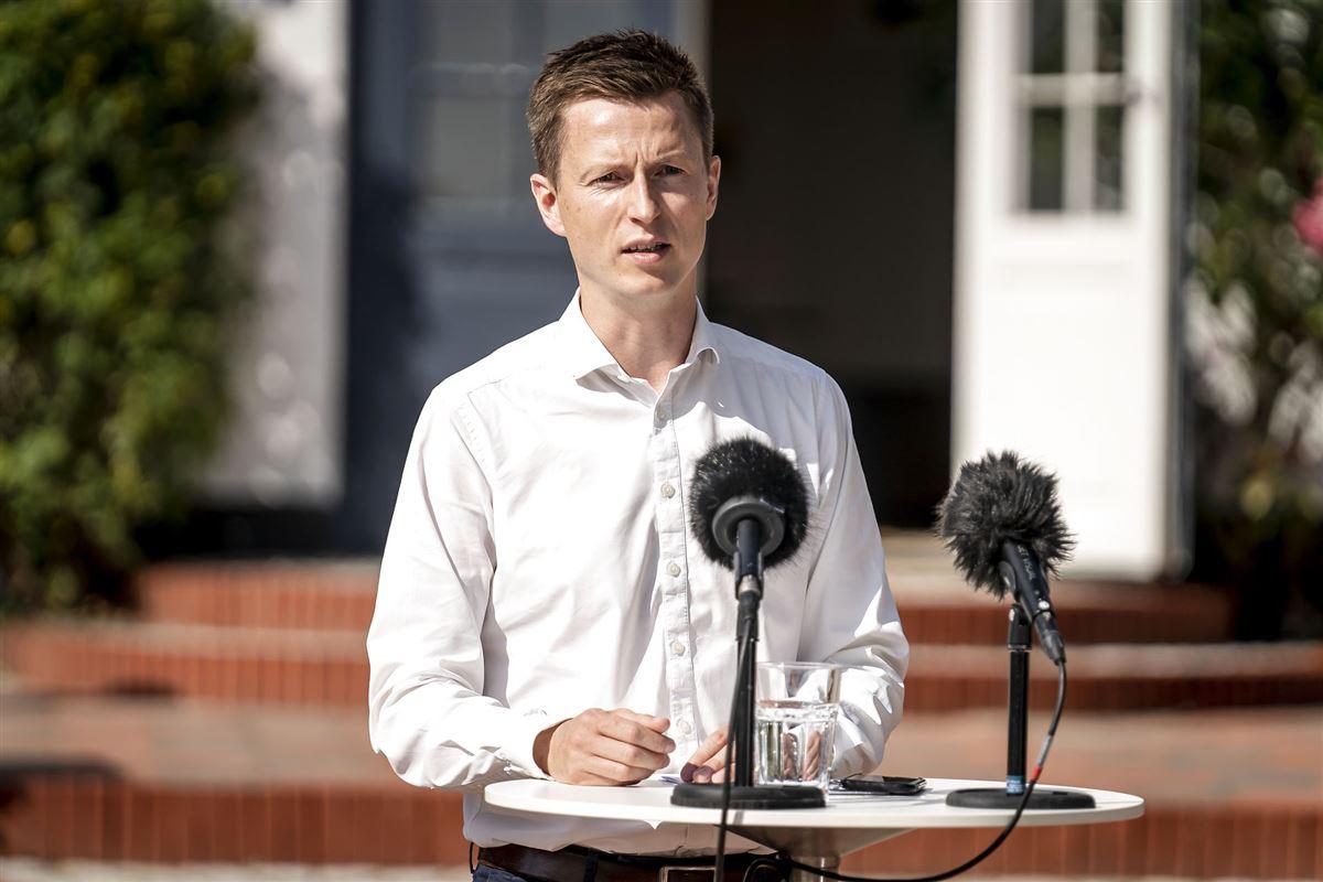 Politikeren Jesper Andersen iført hvid skjorte står ved en udendørs talerstol med to mikrofoner med vindhætter på.