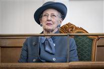Dronningen til åbningen af folketinget. Hun har alvorlig mine i ansigtet og er klædt i en støvet blå jakke med matchende hat.t