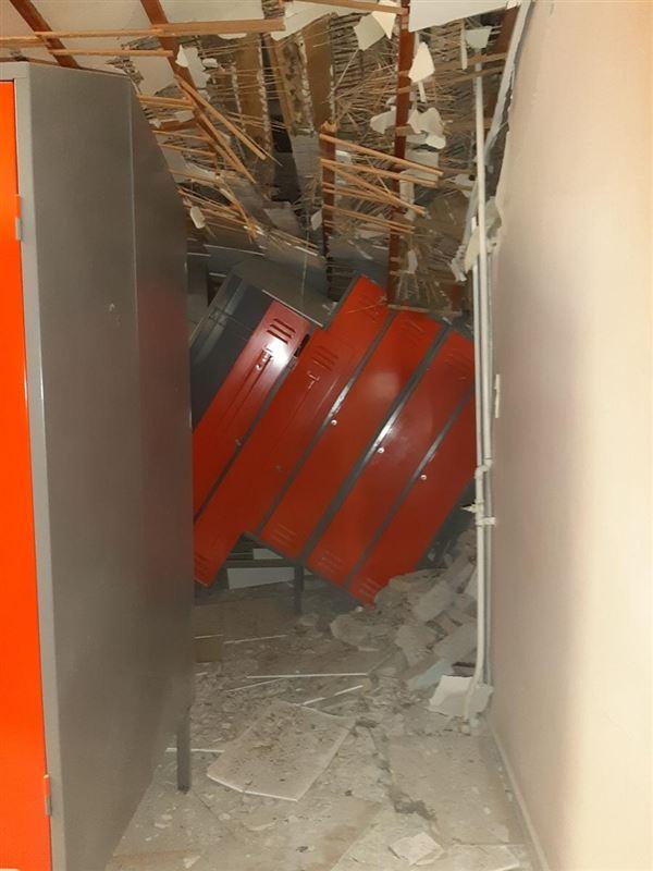fem røde stål skabe står på skrå. De er blevet presset sammen af taget, som er delvis styrtet ned over dem.