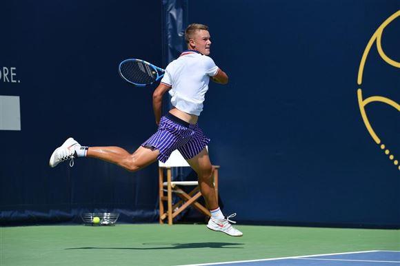 En tennisspiller giver en baghånd på banen