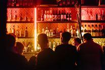 Silhoutter foran en oplyst bar