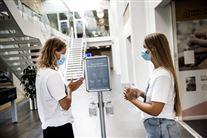 to sundhedspersonaler står og spritter hænder