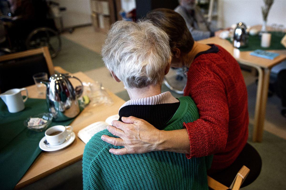 kvinde holder armen rundt om beboer på plejehjem