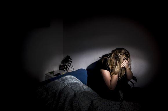 Pige på seng med hænderne for hovedet