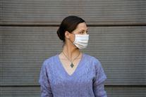 kvinde med mundbind i blå trøje kigger til siden
