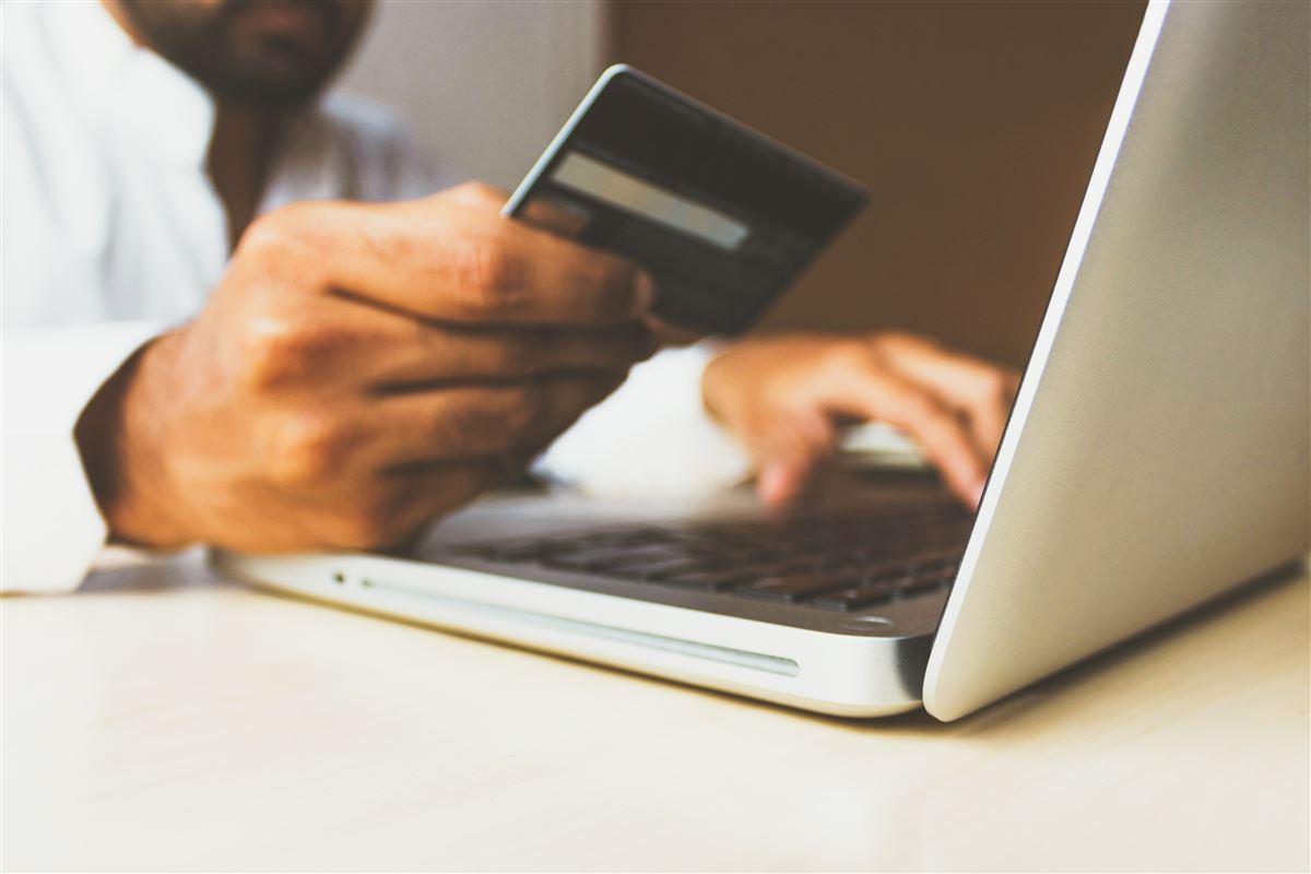 mand sidder med kreditrkort foran computer