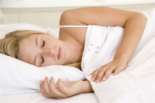 En dame sover i en seng