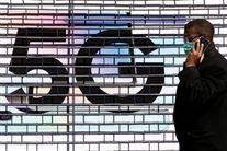 En mand taler i telefon foran et stort 5G-skilt