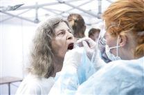 kvinde med åben mund testes for corona
