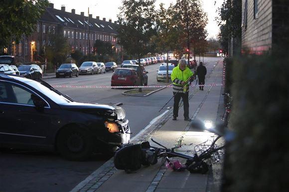 billeder fra stedet, hvor en femårig pige mistede livet. Man ser en politimand i grøn vest spærre af omkring den sorte bil og fortovet.