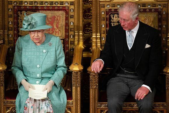 Dronning Elizabeth på en trone med sin søn Charles ved siden af