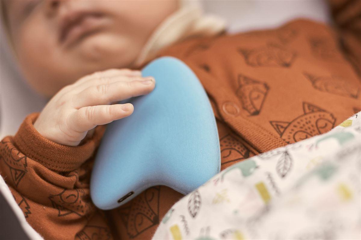 En baby sover med en blå dims ved siden af sig