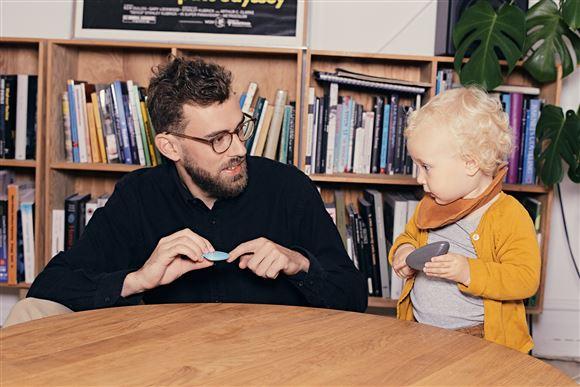 En far med skæg og briller sidder sammen med en lille pige med krøller og gul bluse med bøger i en reol bagved