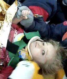 En lille pige ligger på en båre med halskrave på og kigger skræmt ind i kameraet.