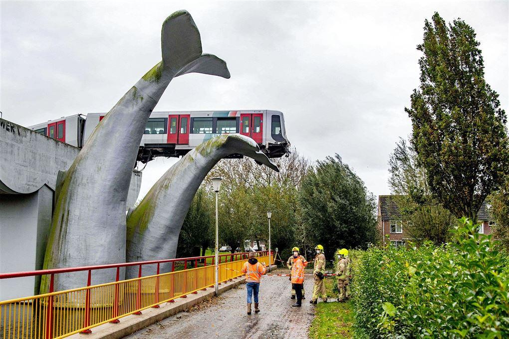 Det afsporede tog set nedefra. Togsættet hviler ti meter over jorden på en hvalhale lavet af beton.