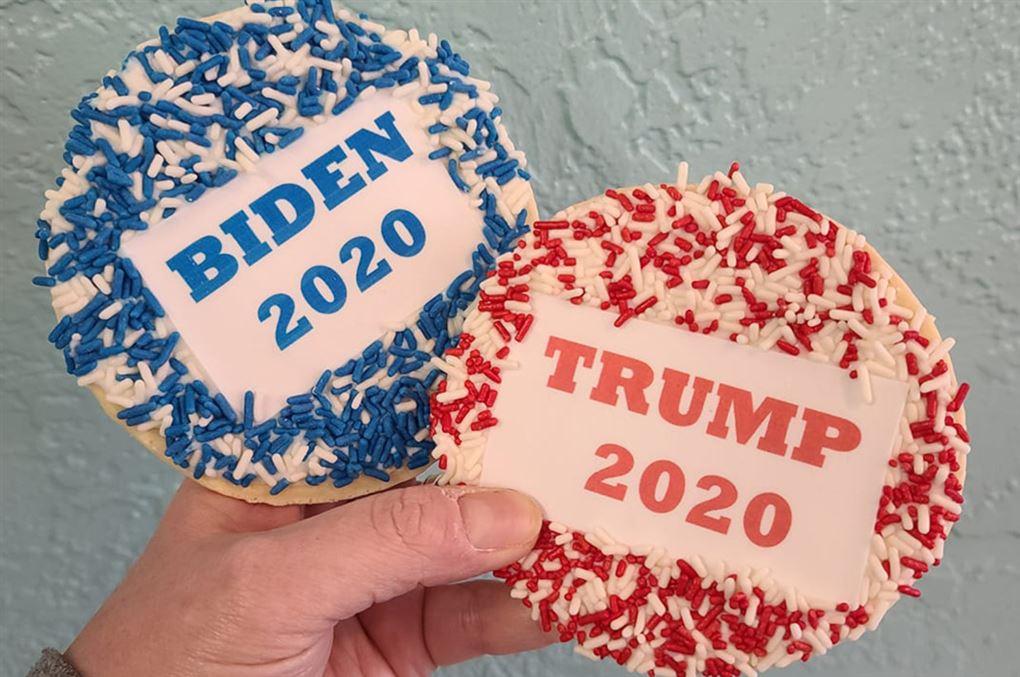 hånd med to kager - en blå og en rød med påskriften Biden 2020 og Trump 2020