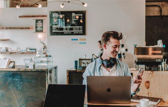 Ung mand sidder bag computer og smiler
