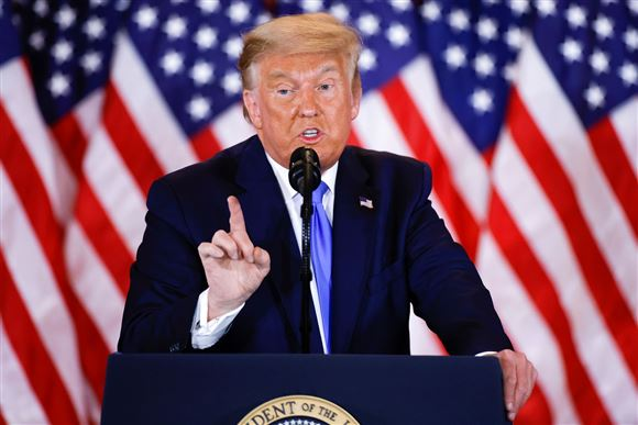 Trump på talerstol med amerikanske flag i baggrunden