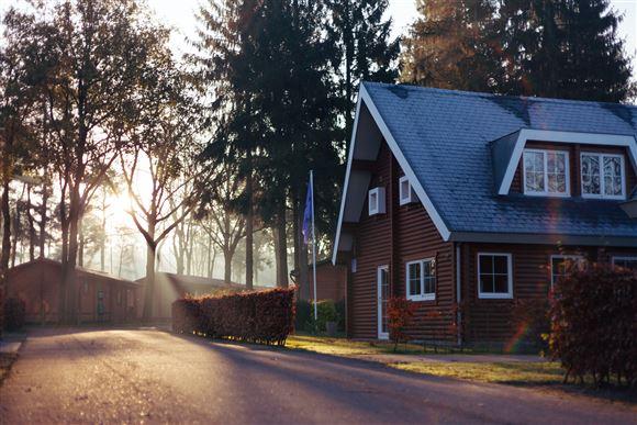 Et smukt rødt hus taget i solopgang med træer bagved