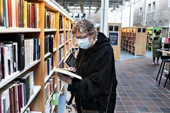 kvinde med briller kigger i bog