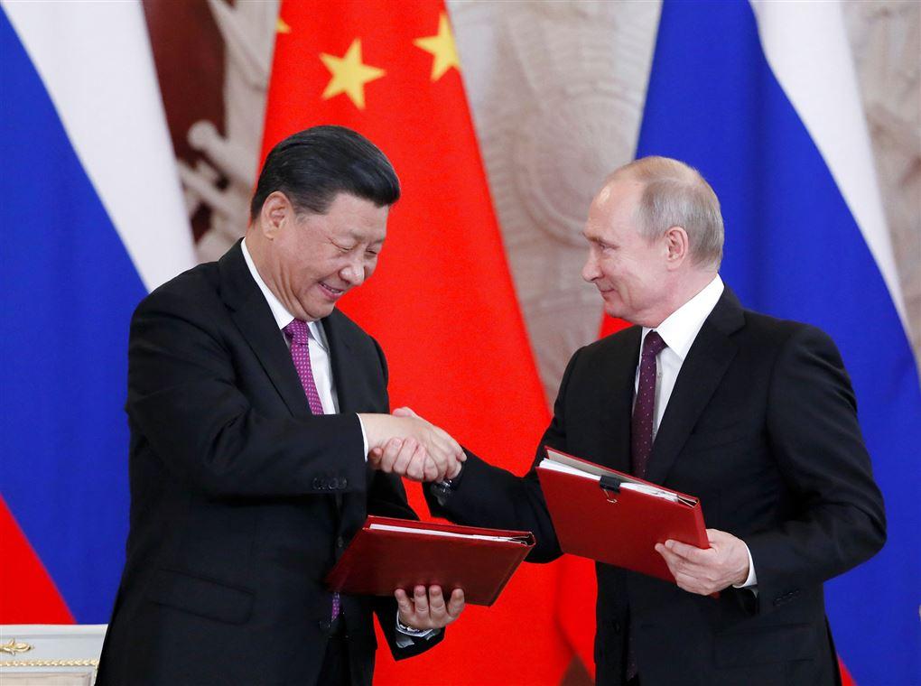 Præsidenterne Ji Xinping og Vladimir Putin giver hinanden et håndtryk