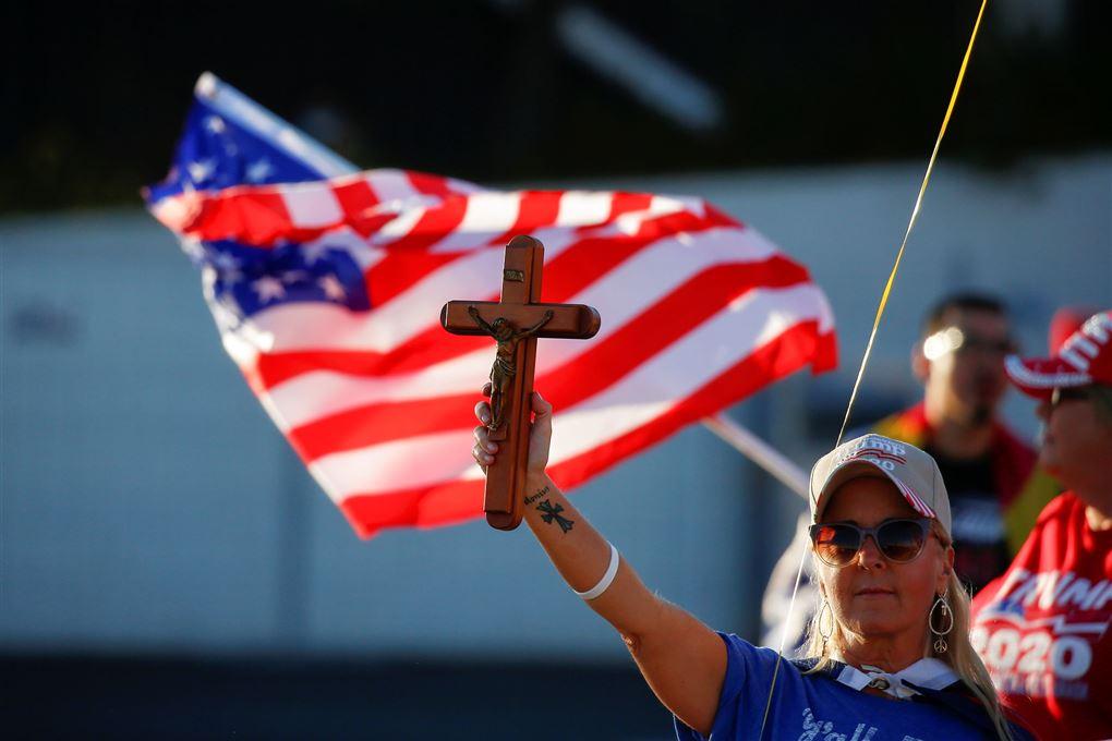 kvinde med krucifiks i strakt arm med det amerikanske flag i baggrunden