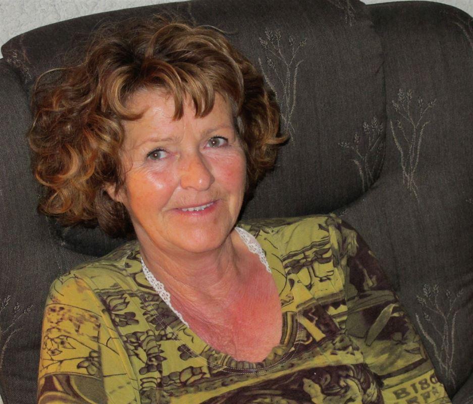 Anne-Elisabeth Hagen portræt, hvor hun sidder i en mørk lænestol og smiler.