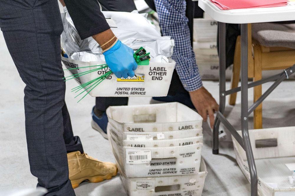 Hvide plastikkasser med brevstemmer i.