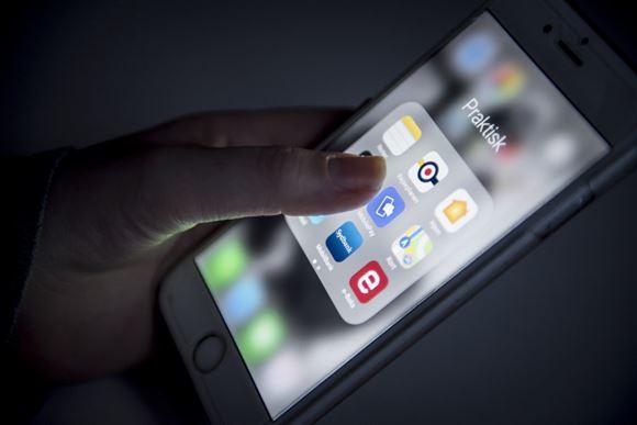 En hånd med en smartphone som trykker på mobilepay ikonet.