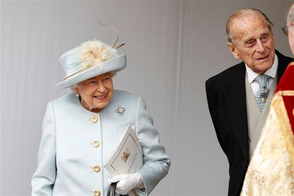 Dronning Elizabeth og prins Philip smiler. Hun har et lyst sæt på med matchende hat.