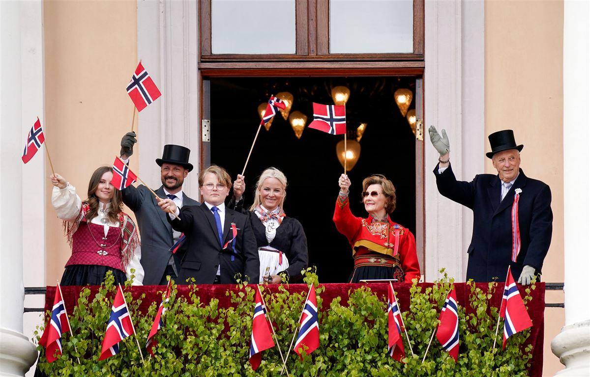 Den norske kongefamilie vinker med norske flag på en balkon. Kvinderne er klædt i nationaldragter.