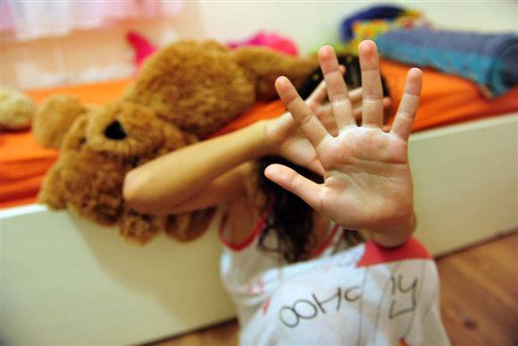 En pige holder sine hænder foran sit ansigt. Hun sidder på gulvet foran en seng, hvor der ligger en tøjbamse.