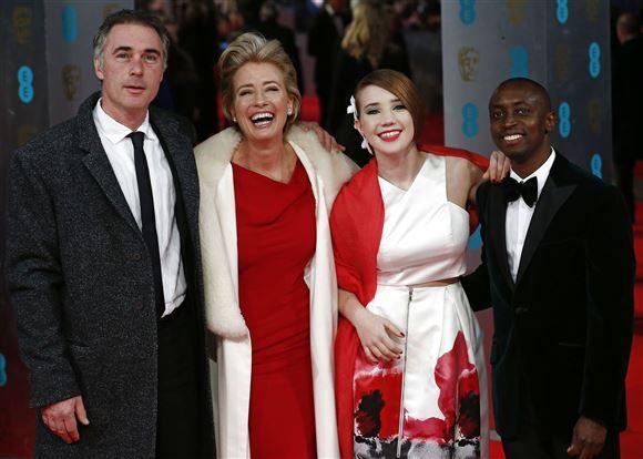 En smilende familie - tre hvide og en sort afrikansk ung mand