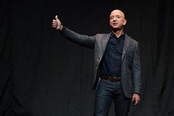 Jeff Bezos står på scene og rækker tommelfingeren i vejret