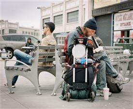 En hjemløs p en bæk ved siden af en ung fyr, som ikke er hjemløs