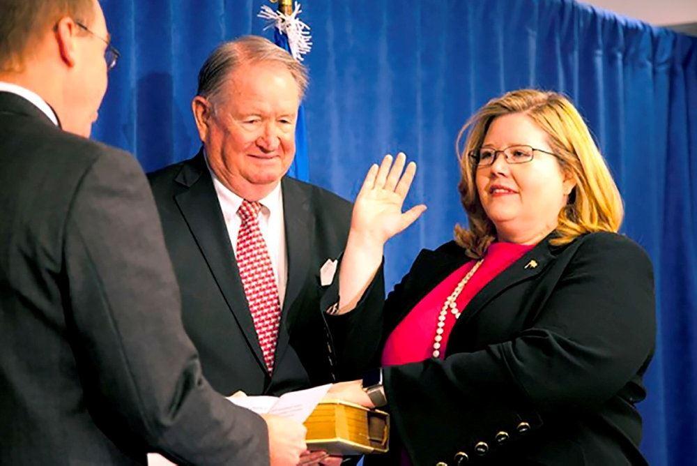 kvinde løfter højre hånd under ceremoni