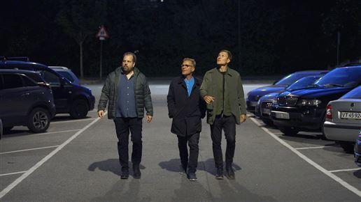 tre mænd går på gaden i mørke