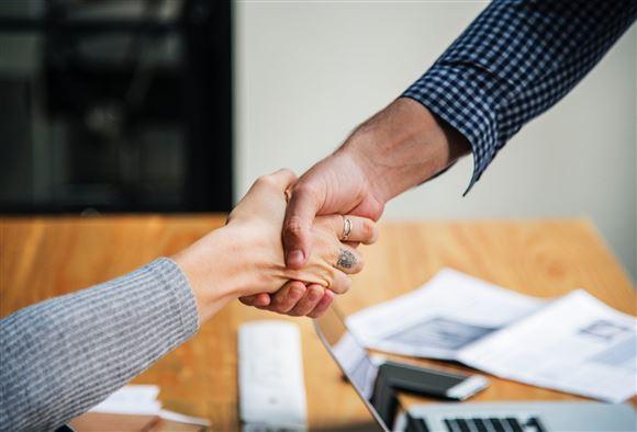 En mand og kvinde giver hinanden hånden