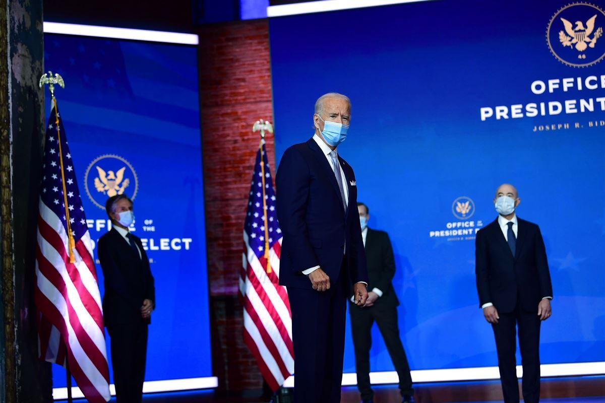 Joe Biden med mundbind foran en række folk ligeledes med mundbind på