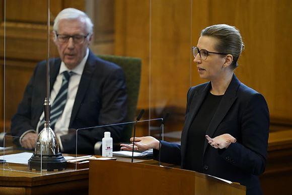 Statsminister Mette Frederiksen gestikulerer på talerstolen i Folketinget