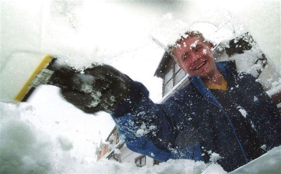 mand skraber is af forruden på en bil