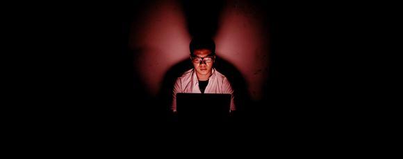 hacker sidder ved skærm