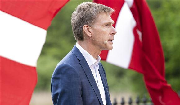 DF's formand Kristen Thulesen Dahl taler ved siden af to danske flag