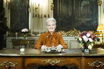 dronning margrethe sidder bag bord