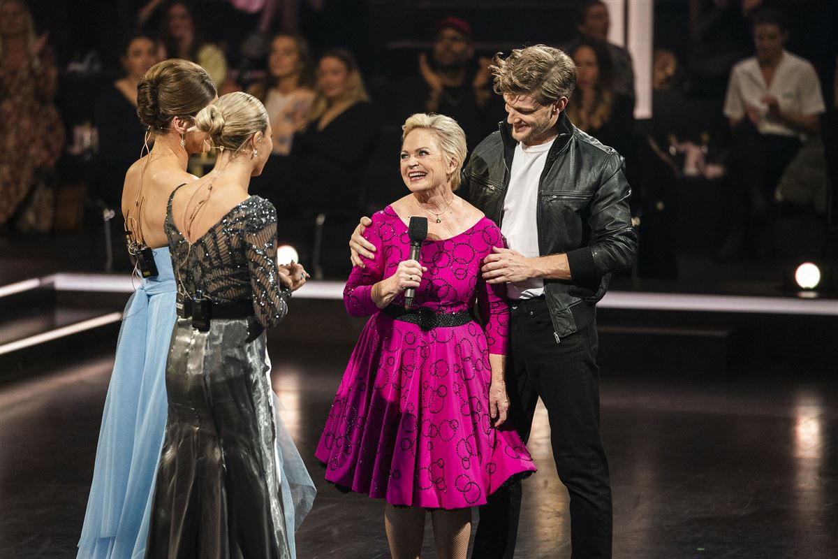Hilda Heick på scenen i rød kjole smiler til sin meddanser og de to værtinder