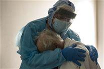 En læge trøster en ældre mand på et hospital.